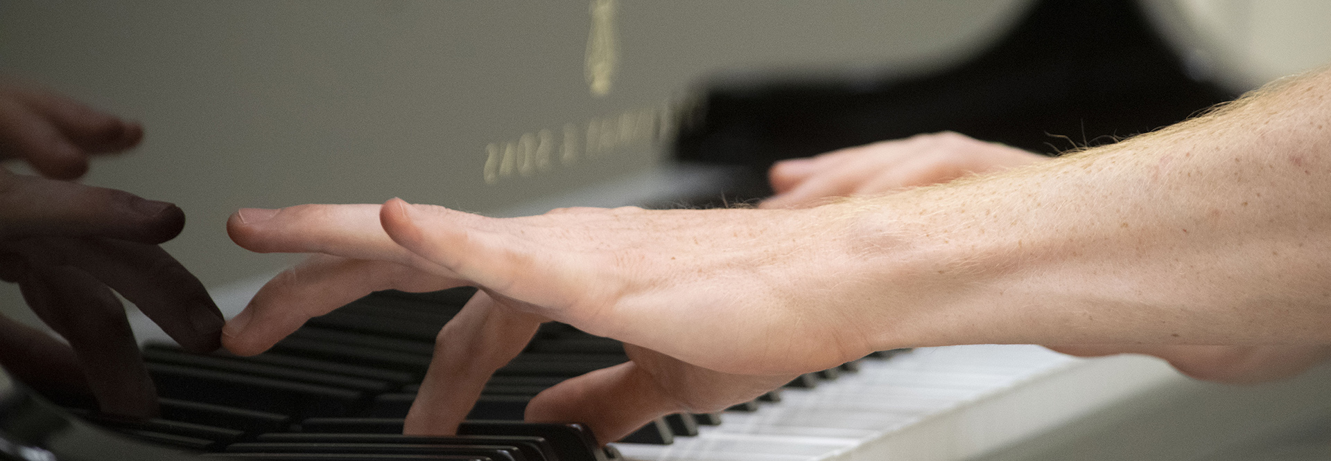 Close up of hands playing a Steinway and Sons Spirio keyboard.