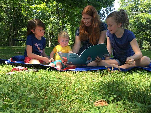 A woman reads a book to her three children while sitting on a lawn under a shade tree.